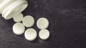 Vitt, grönt, rosa orange kapselpiller som är utspillt från den vita plast- flaskbehållaren globalt sjukvårdbegrepp Antibiotikumma royaltyfria foton