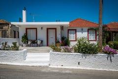 Vitt grekiskt hus med blommor Fotografering för Bildbyråer