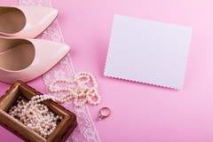 Vitt hälsningkort med den krabba kanten Beigea läderskor med den höga hälet, hälsningkortet och tillbehör på rosa bakgrund Arkivfoton