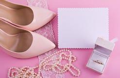 Vitt hälsningkort med den krabba kanten Beigea läderskor med den höga hälet, hälsningkortet och tillbehör på rosa bakgrund Royaltyfria Foton