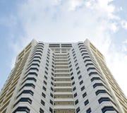 Vitt högt bostads- byggnadshotelltorn och himmel Arkivfoto