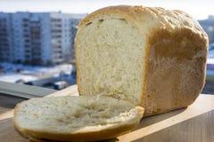 Vitt hemlagat bröd med ett stycke på fönstret arkivfoton