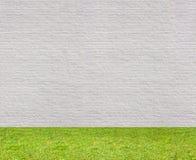 Vitt horisontalsömlöst för tegelstenvägg med gräsmatta Arkivfoton