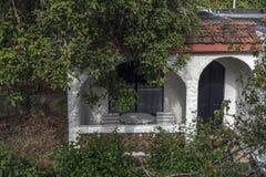 Vitt hus i buskarna Arkivbild