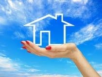 Vitt hus i kvinnahand över blå himmel. Arkivfoton