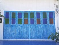 Vitt hus med blåa dörrar och fönster arkivbild