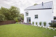 Vitt hus med den rymliga trädgården och grönt gräs under våren Verkligt foto fotografering för bildbyråer