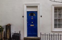 Vitt hus med en blå dörr med en mässingsknackare Royaltyfri Foto