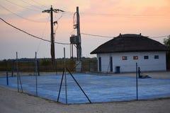 Vitt hus nära ett övergett tennisfält Arkivfoto