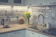 Vitt kök med patchworktegelplattan royaltyfri fotografi