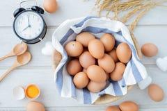 Vitt köksbord med nya rå ägg, ägg för gul äggula, det vita hjärtaformtecknet och den klassiska tappningklockan arkivfoto