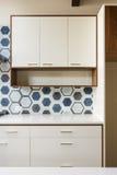 Vitt köksskåp i modernt hem med blåtttegelplattan Royaltyfria Foton