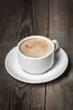 Vitt kaffe rånar med smaklig latte på träyttersida Arkivfoton