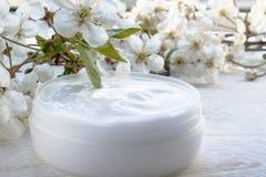 Vitt, kan kosmetisk kr?m och k?rsb?rsr?da blommor p? en vit bakgrund royaltyfri foto