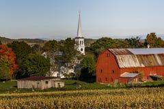 Vitt kapell, röda ladugårdar och lantgårdfält på solnedgången - Peacham, Vermont Arkivbilder