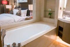 Vitt keramiskt badrum och badkar med badupps?ttningen royaltyfri foto