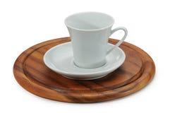 Vitt keramiskt kaffekopp och vittefat på träställning Arkivfoto