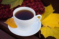 Vitt keramiskt te för kopp C på den gamla trätabellen arkivfoton