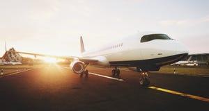 Vitt kommersiellt flygplananseende på flygplatslandningsbanan på solnedgången Den främre sikten av passagerareflygplanet tar av royaltyfri illustrationer