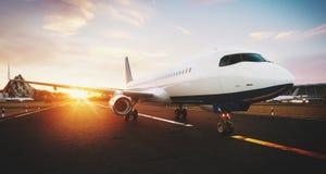 Vitt kommersiellt flygplananseende på flygplatslandningsbanan på solnedgången Den främre sikten av passagerareflygplanet tar av stock illustrationer