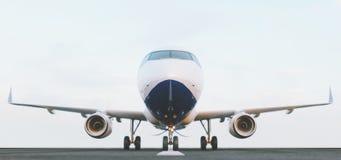 Vitt kommersiellt flygplananseende p? flygplatslandningsbanan p? solnedg?ngen Den fr?mre sikten av passagerareflygplanet tar av stock illustrationer