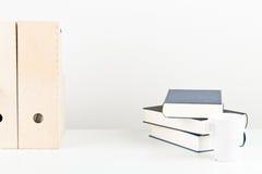 Vitt kontorsskrivbord med böcker, koppen och mappar Royaltyfria Foton