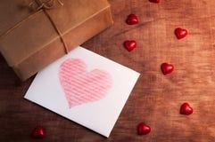 Vitt kort med en hjärta på träbakgrund Arkivbild