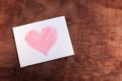 Vitt kort med en hjärta på träbakgrund Royaltyfria Foton