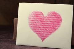 Vitt kort med en hjärta på träbakgrund Arkivbilder