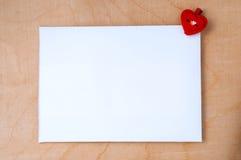 Vitt kort med en liten röd hjärta på träbakgrund Royaltyfri Bild