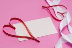 Vitt kort med med kopieringsutrymme, röda hemlagade pappers- hjärtor och ett vitt band på en rosa bakgrund Symbol av dagen för va royaltyfria bilder