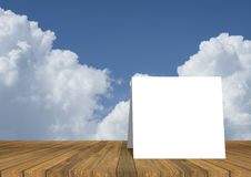 vitt kort på den tomma wood tabellen och härlig blå himmel och moln i bakgrund produktskärmmall 3d business dimensional presentat Arkivfoto