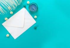 Vitt kuvert med den vita fjädern och pärlor som isoleras på blå bakgrund Begrepp f?r h?lsningkort arkivfoto