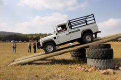 Vitt land Rover Defender 110 HC på kursen 4x4 Royaltyfri Fotografi