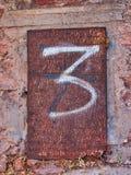 Vitt målat husnummer för nummer 3 arkivfoton