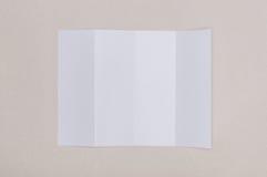 Vitt mallpapper för fyra veck på grå bakgrund Fotografering för Bildbyråer