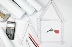Vitt meterhjälpmedel som bildar ett hus och iscensätter hjälpmedel på vit Royaltyfri Fotografi