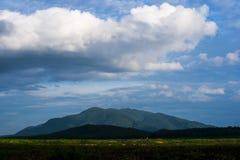 Vitt moln över bergsikt Arkivfoton