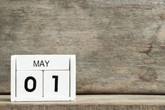Vitt närvarande datum 1 för kvarterkalender och månad Maj på träbakgrund royaltyfri foto
