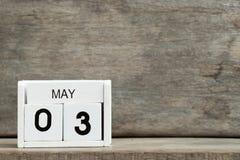 Vitt närvarande datum 3 för kvarterkalender och mÃ¥nad Maj pÃ¥ träbakgrund fotografering för bildbyråer