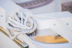 Vitt nautiskt rep som binds på dubben av det moderna yachtdäcket royaltyfri bild
