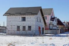 Vitt oavslutat tegelstenhus på en byggnadsplats i snön arkivbilder