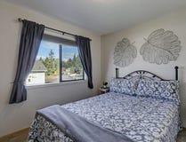 Vitt och grått sovrum med järnsäng Fotografering för Bildbyråer