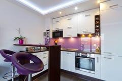 Vitt och purpurt kök med strålkastarear Arkivbilder