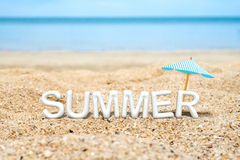 Vitt ord för sommar (text för tolkning 3D) med strandparaplyet på san Royaltyfri Fotografi