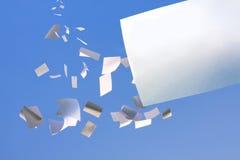 Vitt papper som faller från den klara blåa skyen. Royaltyfri Bild