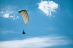 Vitt paragliderflyg i den blåa himlen mot bakgrunden av moln Arkivfoto