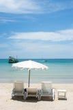 Vitt paraply på den trevliga sandstranden Arkivbild