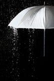 Vitt paraply under regndroppar med svart bakgrund Royaltyfri Fotografi