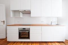 Vitt pentry, frontal sikt för nyligen inbyggt kökmöblemang med träworktop- och brädegolvet royaltyfria foton
